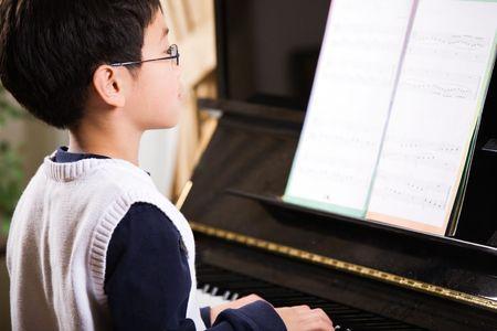 piano: Una foto de un ni�o asi�tico tocando el piano