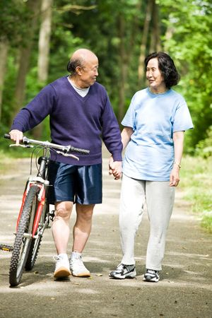 A senior active asian couple walking and exercise at the park