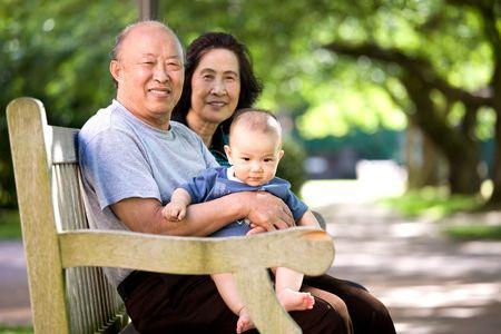 abuelos: Una foto de un lindo ni�o asi�tico con sus abuelos en un parque Foto de archivo
