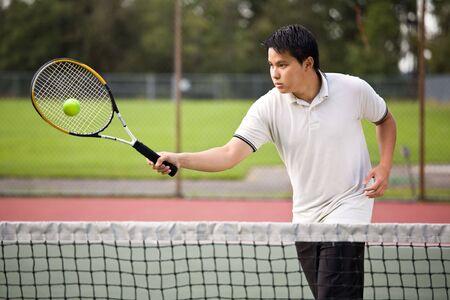 Een Aziatische tennis speler raakt de bal