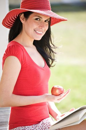 A beautiful hispanic woman reading a book and eating an apple outdoor Stock Photo - 4662525