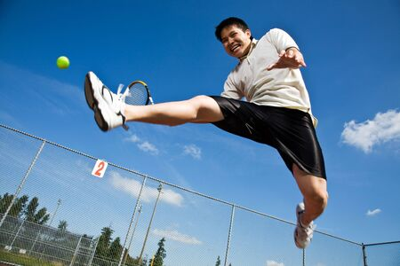 An asian tennis player jumping in the air hitting a tennis ball Reklamní fotografie - 4702052