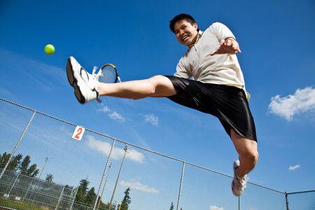 tennis stadium: Un jugador de tenis de Asia saltando en el aire golpeando una pelota de tenis