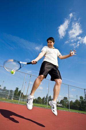 tennis stadium: Un jugador de tenis de Asia saltando en el aire, golpeando una pelota de tenis