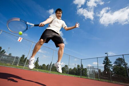 jugando tenis: Un jugador de tenis de Asia saltando en el aire golpeando una pelota de tenis