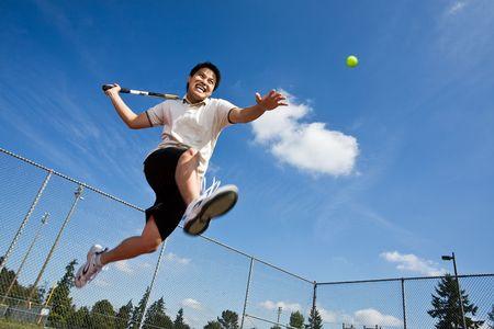 tenis: Un jugador de tenis de Asia saltando en el aire golpeando una pelota de tenis