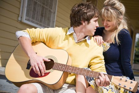 A young caucasian man in love playing guitar and singing to his girlfriend photo