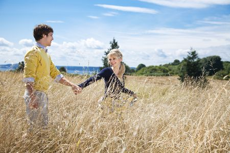 A young caucasian couple in love having fun on a grassy field photo