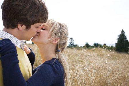 parejas jovenes: Un joven caucasian joven en el amor beso al aire libre
