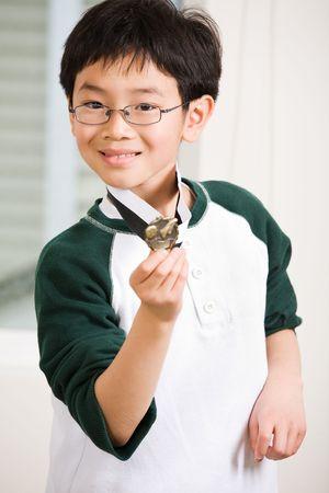 An asian boy showing his winning sport medal photo