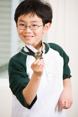 An asian boy showing his winning sport medal Stock Photo