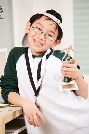 An asian boy showing his winning sport medal and trophy photo