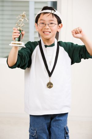 An asian boy excited aboyt his winning sport medal and trophy photo