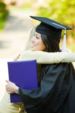 A happy beautiful graduation girl being congratulated by her friend photo