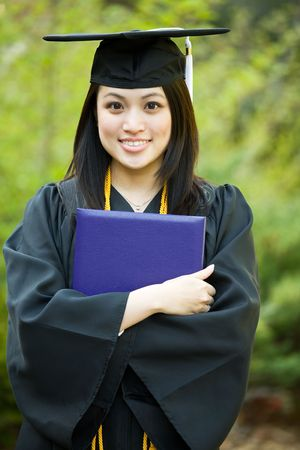licenciatura: Una feliz ni�a hermosa graduaci�n sosteniendo su diploma Foto de archivo