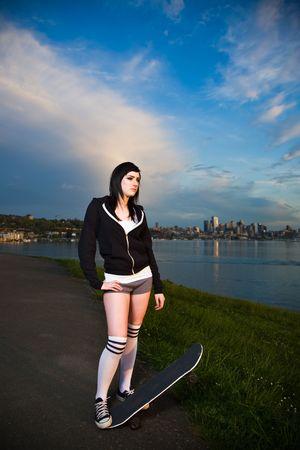 屋外、日没時に美しい白人スケーター十代の少女 写真素材