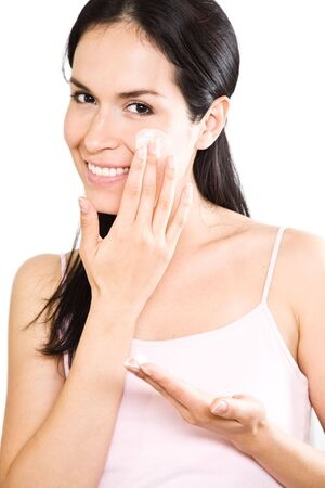 woman face cream: A beautiful hispanic woman applying lotion to her face in the bathroom Stock Photo