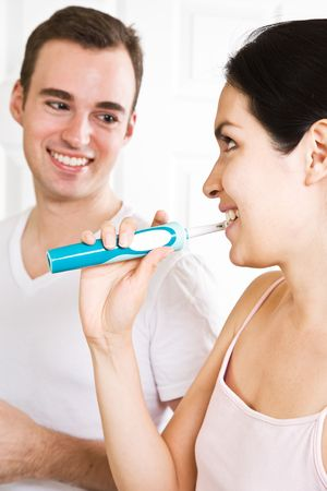 A beautiful interracial couple in the bathroom brushing teeth photo