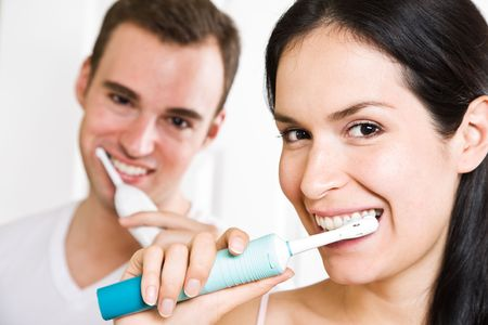 A beautiful interracial couple in the bathroom brushing teeth Stock Photo