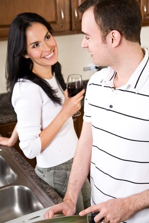 A beautiful interracial couple preparing food and having a conversation in the kitchen photo