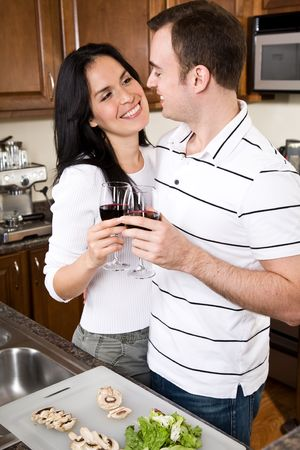 A beautiful interracial couple preparing food in the kitchen Stock Photo - 4815599