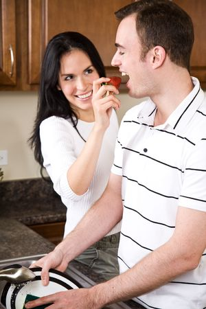 A beautiful interracial couple together in the kitchen Stock Photo - 4815595