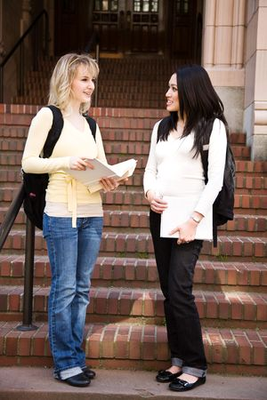 Two college students meeting and talking on campus photo