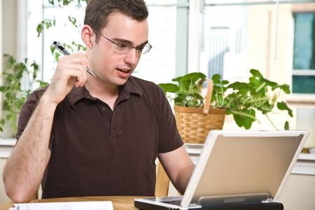 A caucasian man paying the bills by online banking at home photo