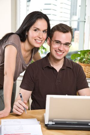 paying: A happy couple paying bills by using online banking at home