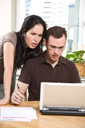 A stressed couple paying bills by using online banking at home Stock Photo - 4843712