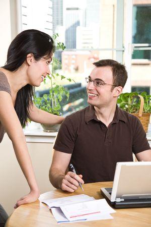 A happy couple paying bills by using online banking at home photo