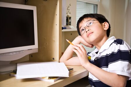 A shot of an asian kid studying at home Banco de Imagens