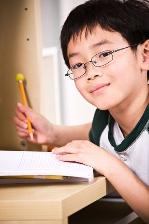 person writing: A shot of an asian kid studying at home Stock Photo
