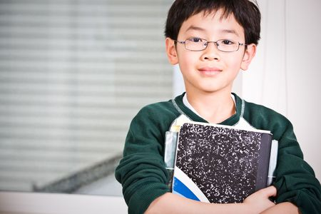 A shot of an asian kid carrying books Stock Photo