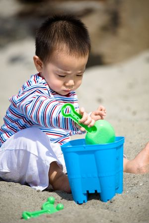 A cute asian boy playing with sand on the beach