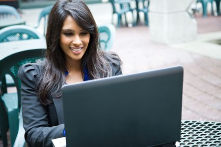working office: A shot of an indian businesswoman working on her laptop outdoor