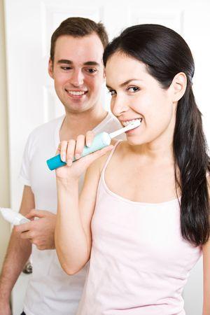 couple bathroom: A beautiful interracial couple in the bathroom brushing teeth Stock Photo