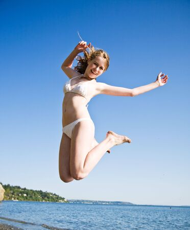 A beautiful caucasian girl jumping in joy on the beach during summer Stock Photo