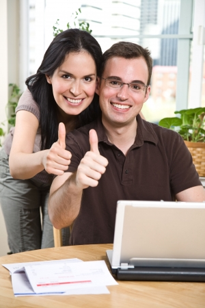 A happy couple paying bills by using online banking at home giving thumbs up Imagens