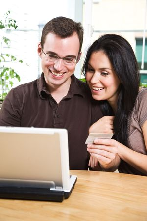 hispanic women: A happy couple holding a credit card shopping online Stock Photo
