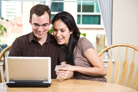 buying online: A happy couple holding a credit card shopping online Stock Photo