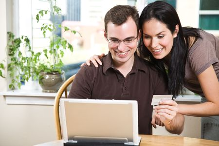 shopper: A happy couple holding a credit card shopping online Stock Photo