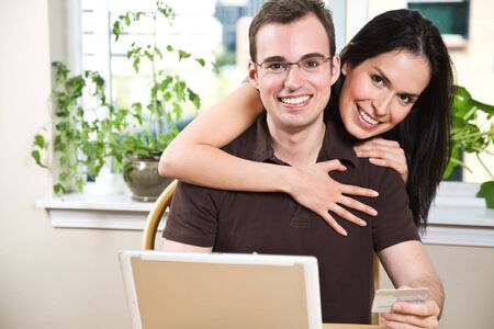 A happy couple holding a credit card shopping online photo