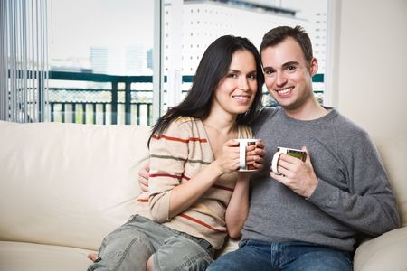 A happy couple sitting on the couch at home enjoying coffee photo