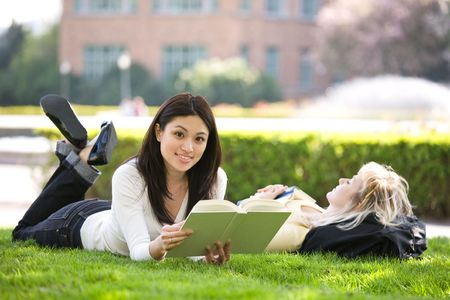 campuses: A shot of two college students studying on campus
