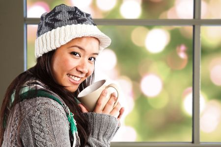 winter fashion: A shot of a happy beautiful asian woman drinking coffee