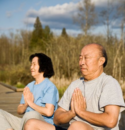 An active senior asian couple exercises and practices yoga and meditation photo