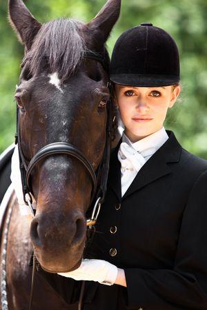 그녀의 말과 함께 포즈를 취하는 승마를 준비하는 백인 소녀