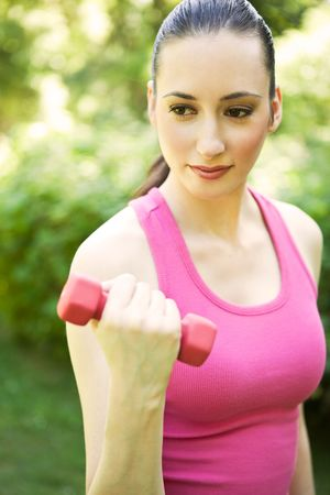 A beautiful caucasian woman doing exercise with dumbbells in a park Stock Photo - 5150676