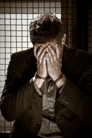 prision: Un hombre de negocios caucasian sesi�n esposado en la c�rcel